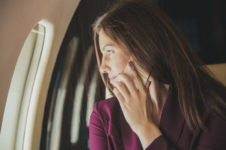Young woman sits in a plane near the window Reklamní fotografie