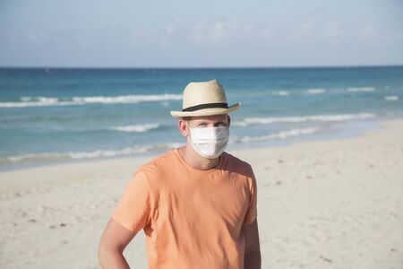 A man with a medical protective mask for coronavirus on the beach in a tropical country at summer sunny day Reklamní fotografie