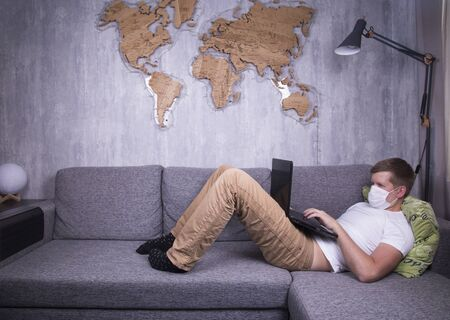man in quarantine for Coronavirus wearing protective medical mask and smart working at home