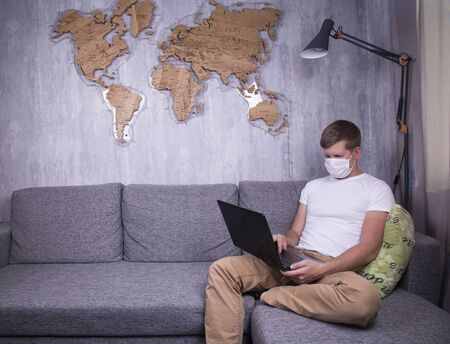 A man in quarantine for Coronavirus wearing protective medical mask and smart working at home Reklamní fotografie