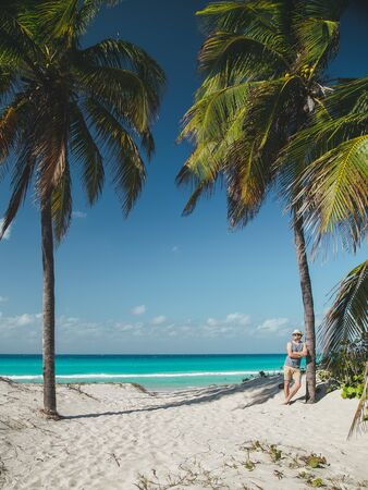younge man stay near the palm on the ocean beach of tropical island at sunny day