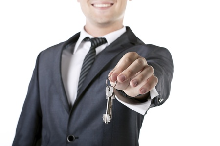 Businessman with a house key in hand isolated on white photo