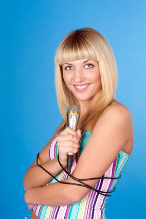 Beautiful blond young woman singing into a microphone photo