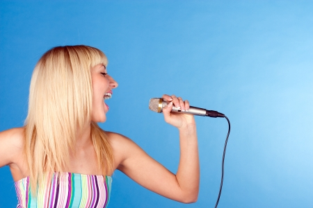 Funny blonde on a blue background with a microphone