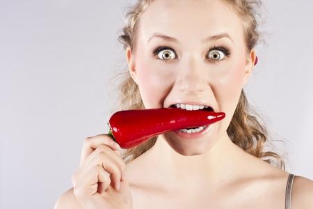 Beautiful woman teeth eating red hot chili pepper photo