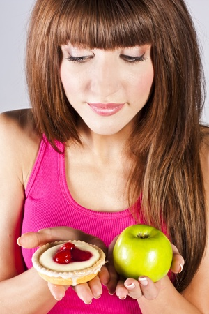Woman with apple and cake in hands