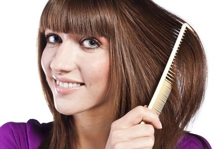 Brunette brushing her hair, in studio