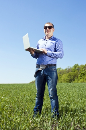 Businessmanon meadow, with a laptop photo