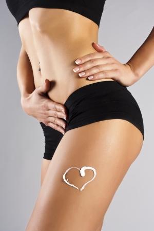 Woman applying moisturizer cream on legs  Perfect female figure Stock Photo