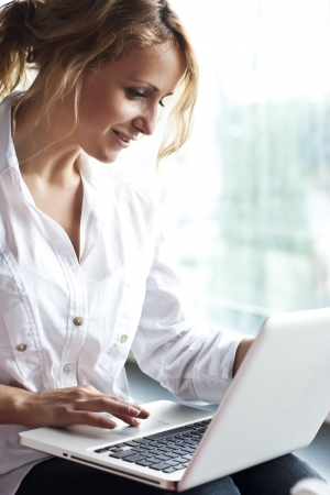 Happy young beautiful woman with laptop - indoors  photo