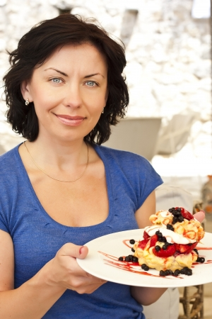 cafe bistro: Woman eating delicious dessert  in a cafe bistro