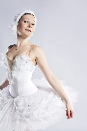 Beautiful ballerina posing on grey photo