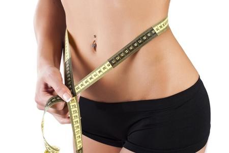 Thin young woman measures the waist Standard-Bild