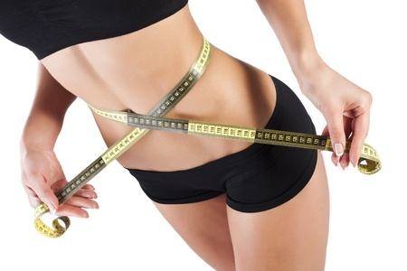 body care: Thin young woman measures the waist Stock Photo