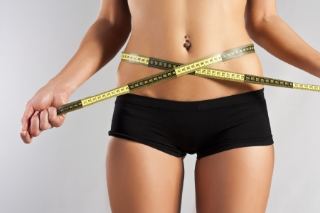 Thin young woman measures the waist Stock Photo