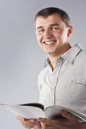 Young man reading a book, isolated on grey photo