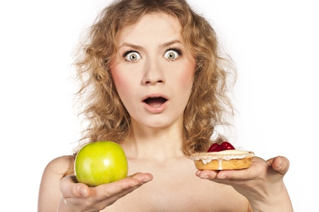 Young cheerful woman, choosing between apple and cake photo