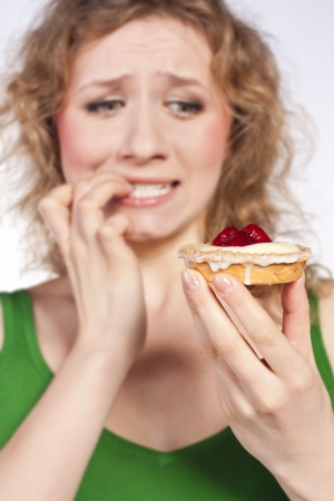 Woman eating a cake  In studio photo