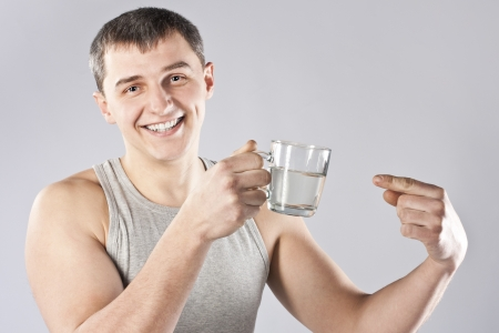 Young handsome man drinking mineral water photo