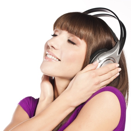 Young attractive woman, dancing to music, with headphones against white background photo
