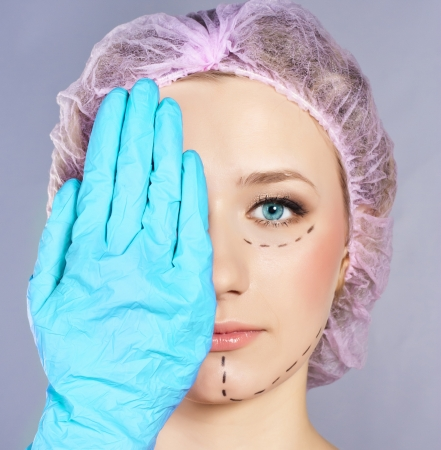 Plastic surgery hand touching the beautiful woman face.  Model is european beauty