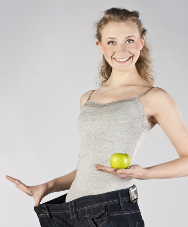 Woman after diet, in old big jeans, with green apple and orange Stock Photo - 18912037