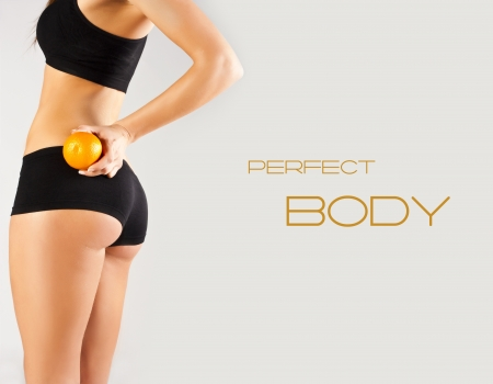 female body: Perfect body. Woman holding an orange