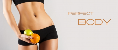 Dieting concept, Beautiful belly and a fruit isolated on grey Stock Photo