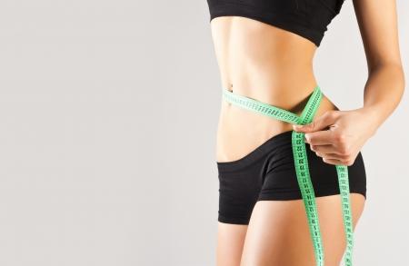 Girl measuring, perfect shape of beautiful thigh. Studio