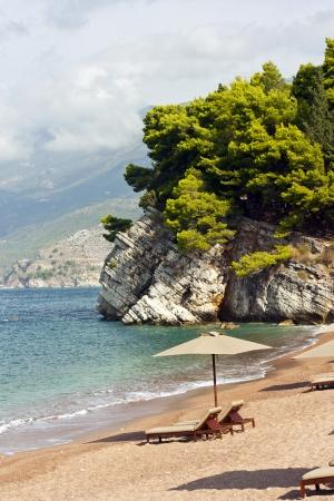 Sveti Stefan island in Montenegro  Canvas chairs on the beach photo