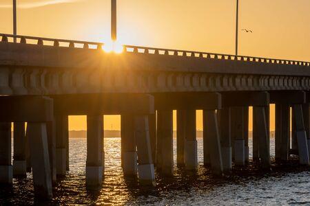 View of the sun rising over a bridge Stock Photo
