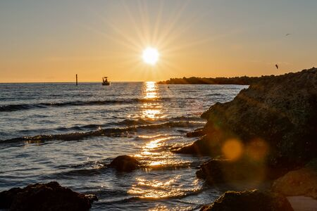 Rays from the sun make a silhouette of a boat and the rocky shore