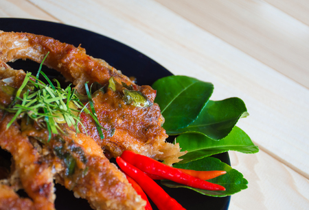 Close up of fried fish with chili sauce on a black plate. Thai food style Archivio Fotografico