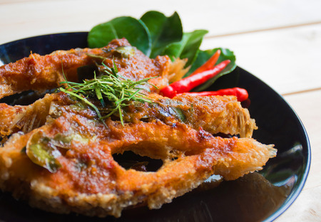 fish sauce: Close up of fried fish with chili sauce on a black plate. Thai food style Stock Photo