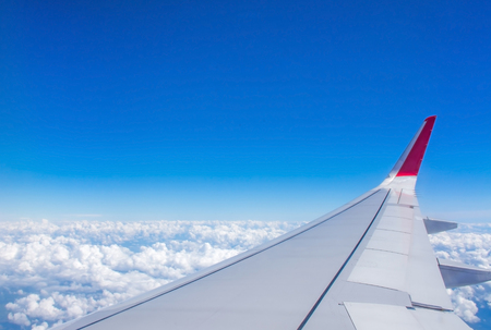through the window: Clouds and blue sky as seen through window of an aircraft. Travel concept