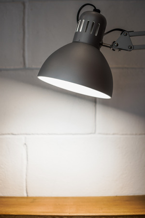 blank spaces: Lamp with blurred white brick background and wood