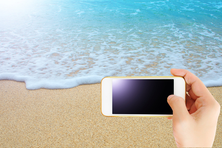 Hand hold smartphone with beautiful blue sea and sand, Travel concept. with clipping path of tuch screen. 스톡 콘텐츠