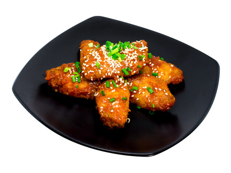Fried Chicken with Korean Sauce on black dish isolated on the white background.