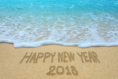 Happy new year 2018 written on sandy beach, New Year 2018 is coming concept.
