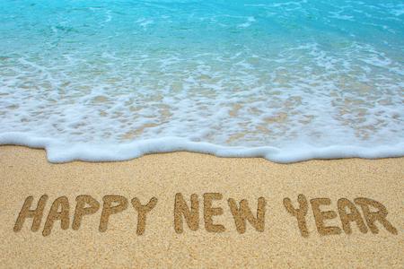 Happy new year written on sandy beach.