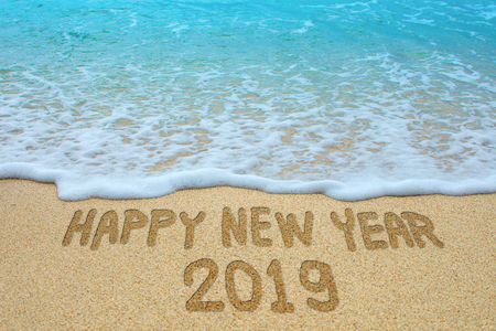 Happy new year 2019 written on sandy beach, New Year 2019 is coming concept.