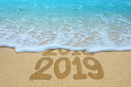 2018 and 2019 written on sandy beach, the wave is covering 2018. New Year 2019 is coming concept.