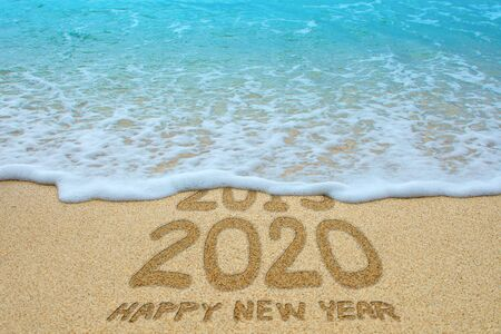 Happy new year 2020 written on sandy beach, New Year 2020 is coming concept.