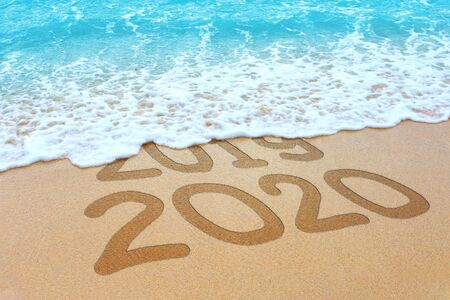 2019 and 2020 written on sandy beach, New Year 2020 is coming concept.