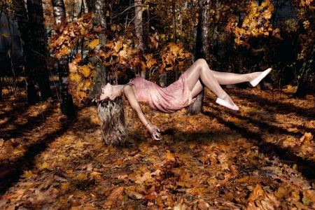 levitacion: Hermosa mujer volando con Auumn deja Levitaci�n Foto de archivo