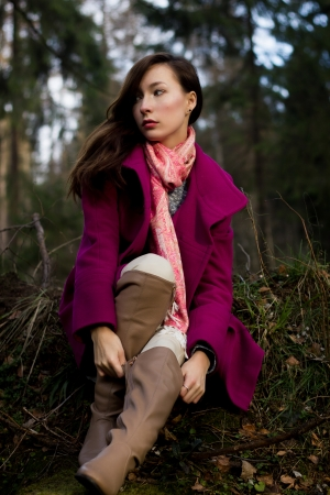 topcoat: Well-dressed young woman in pink topcoat sitting in forest