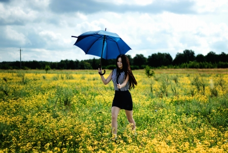 Happy girl running yellow flowers field with blue umbrella photo
