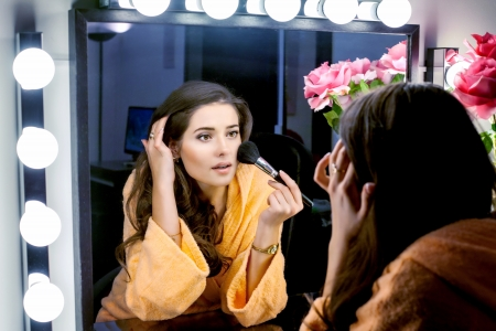 Woman in orange robe doing her makeup and wathching in mirror photo