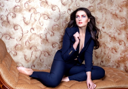 Sexy woman in suit on vintage couch photo