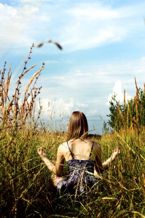oneness: Relaxed woman doing yoga in sunny field